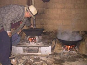 Improved cooking stove and fireplace for the Yi community. Many of their villages are at high altitude, so space heating is often required. A traditional Yi cookstove is shown on the right. Photo - The Nature Conservancy